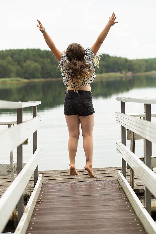 Ein Mädchen spring freudig auf einem Steg