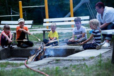 Frau Reichel sitzt mit ein paar Kindern am Lagerfeuer und grillen Stockbrot