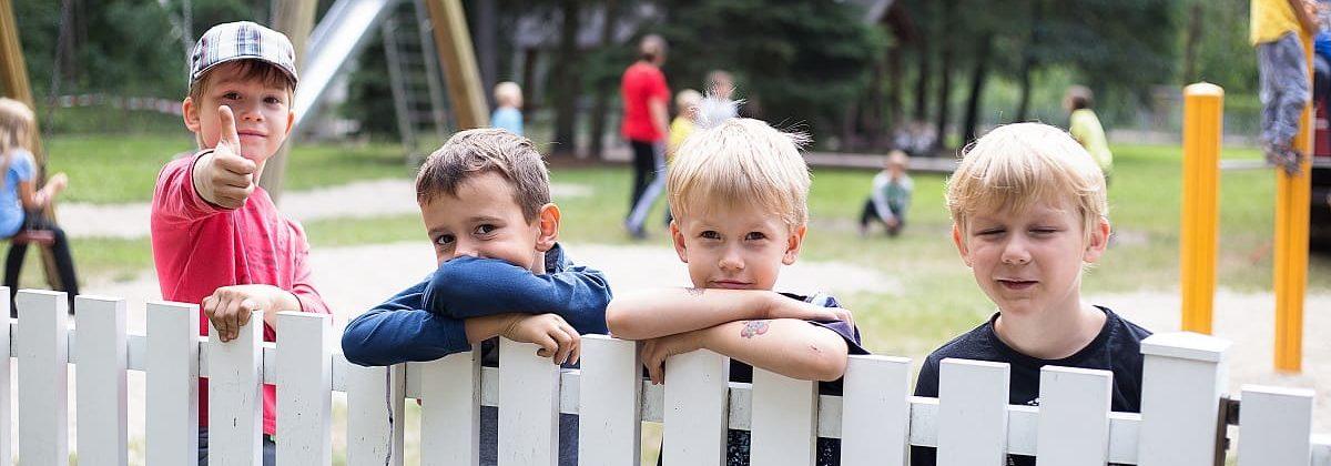 4 Jungs lehnen sich an einen weißen Zaun