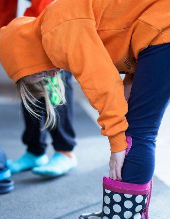 Ein Mädchen zieht sich Ihre Gummistiefel an